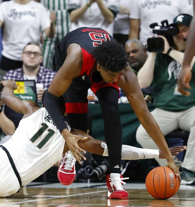 Michigan State forward Aaron Henry (11) and Rutgers center Myles Johnson (15) reach for the loose ball during the first half of an NCAA college basketball game Wednesday, Feb. 20, 2019, in East Lansing, Mich. (AP Photo/Carlos Osorio)