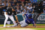 Chicago White Sox third baseman Yoan Moncada, left, tags out Texas Rangers' Scott Heineman as umpire Ramon De Jesus, right, watches during the third inning of a baseball game Thursday, Aug. 22, 2019, in Chicago. (AP Photo/Jeff Haynes)