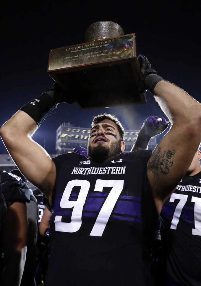 Northwestern defensive line Joe Gaziano celebrates as he holds the Land of Lincoln Trophy after Northwestern defeated Illinois 24-16 in an NCAA college football game in Evanston, Ill., Saturday, Nov. 24, 2018. (AP Photo/Nam Y. Huh)