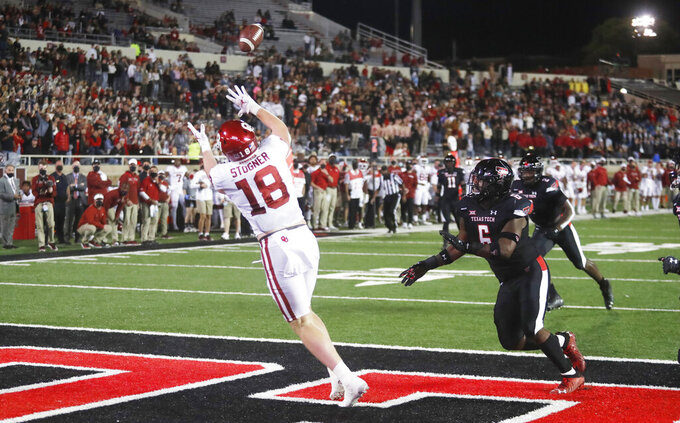Oklahoma's Austin Stogner makes a touchdown catch in the end zone during the first half of the team's NCAA college football game against Texas Tech, Saturday, Oct. 31, 2020, in Lubbock, Texas. (AP Photo/Mark Rogers)