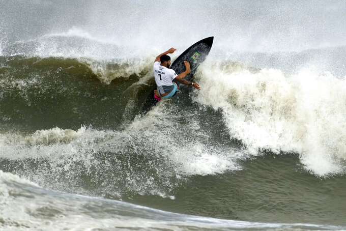 Brazil's Italo Ferreira preforms on the wave during the gold medal heat in the men's surfing competition at the 2020 Summer Olympics, Tuesday, July 27, 2021, at Tsurigasaki beach in Ichinomiya, Japan. (AP Photo/Francisco Seco)