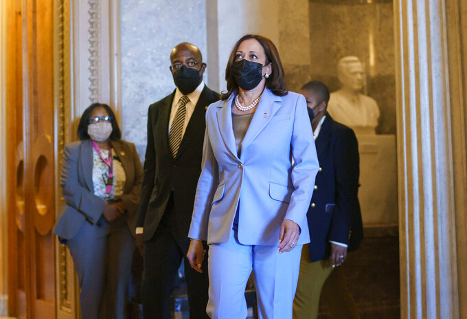 Vice President Kamala Harris, joined by Sen. Raphael Warnock, D-Ga., left, departs the Senate as lawmakers work to advance the $1 trillion bipartisan infrastructure bill, at the Capitol in Washington, Monday, Aug. 2, 2021. The 2,700-page bill includes new expenditures on roads, bridges, water pipes broadband and other projects, plus cyber security. (AP Photo/J. Scott Applewhite)