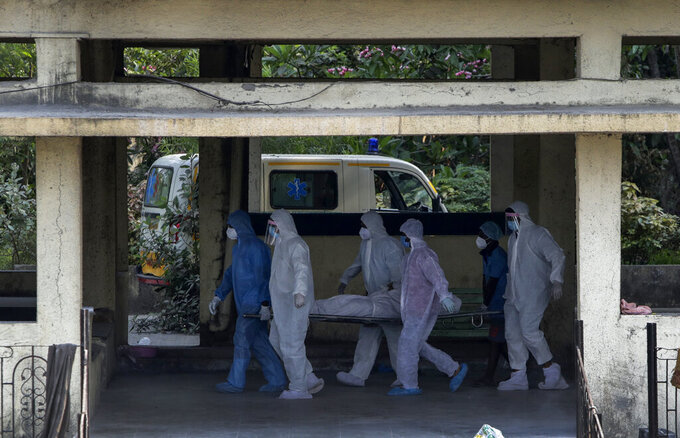 FILE - In this April 13, 2021, file photo, the body of a person who died of COVID-19 is brought for cremation at the Vasai crematory in Palghar, near Mumbai, India. The global death toll from the coronavirus topped a staggering 3 million people Saturday, April 17, 2021, amid repeated setbacks in the worldwide vaccination campaign and a deepening crisis in places such as Brazil, India and France.  (AP Photo/Rajanish Kakade, File)
