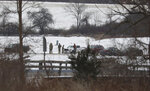 Authorities gather near the wreckage of a UH-60 Black Hawk medical evacuation helicopter in a field in Mendon, NY., Thursday, Jan. 21, 2021. Three National Guard members were killed in the crash Wednesday evening Jan. 20. (Tina MacIntyre-Yee/Democrat & Chronicle via AP)