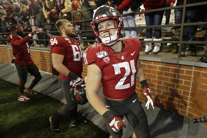 FILE - In this Nov. 23, 2019, file photo Washington State running back Max Borghi (21) celebrates with fans after Washington State defeated Oregon State 54-53 in an NCAA college football game in Pullman, Wash. Borghi is likely to get more rushing attempts under the new Washington coach Nick Rolovich. Borghi was an All-Pac-12 honorable mention last season after recording 1,435 all-purpose yards and 16 total touchdowns, second-most in the league. (AP Photo/Ted S. Warren,File)