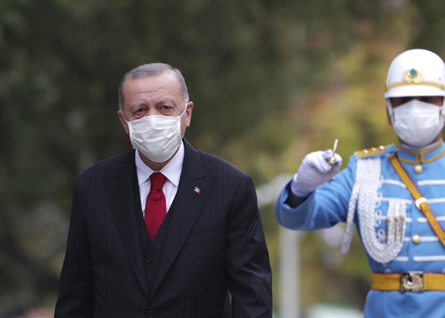 Turkey's President Recep Tayyip Erdogan, wearing a face mask to help prevent the spread of the coronavirus, inspects a military honour guard at the parliament, in Ankara, Turkey, Thursday, Oct. 1, 2020. Turkey's government is being accused of hiding the true extent of the country's coronavirus outbreak after the health minister revealed that the daily COVID-19 figures published by his ministry reflect only patients with symptoms and not all positive cases. (Turkish Presidency via AP. Pool)