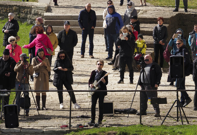 Estonian guitarist Jaak Sooaar performs in the Narva Castle on the Russian-Estonian border in Narva, Estonia, Friday, April 30, 2021. Musicians on the Estonian-Russian border held an unusual concert on Friday, with Estonian guitarist Jaak Sooaar and Russian saxophonist Alexey Kruglov performing from the castles on the opposing banks of the Narva river that marks the border between the two countries. The concert was held on the International Jazz Day by the two musicians as an act of friendship despite the deteriorating relations between the two countries and as cross-border contacts have been limited due to the corona-virus pandemic. (AP Photo/Dmitri Lovetsky)
