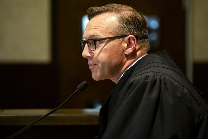 FILE - In this Aug. 26, 2019 file photo, Judge Thad Balkman reads a summary of his decision in the opioid trial at the Cleveland County Courthouse in Norman, Okla. Judge Balkman reduces amount Johnson & Johnson must pay state to help clean up opioid crisis by $107 million to $465 million on Friday Nov. 15, 2019. (Chris Landsberger/The Oklahoman via AP, Pool)