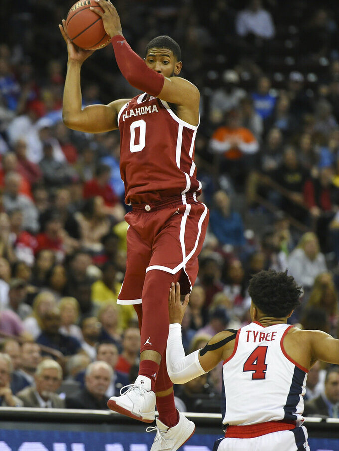 Oklahoma's Christian James (0) goes up for a pass while defended by Mississippi's Breein Tyree (4)  during a first round men's college basketball game in the NCAA Tournament in Columbia, S.C. Friday, March 22, 2019. (AP Photo/Richard Shiro)