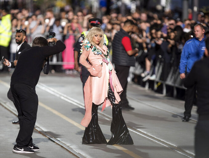 """FILE - Lady Gaga  is surrounded by press and security as she walks down Toronto's King Street for the screening of """"Gaga: Five Foot Two"""" at the Toronto International Film Festival in Toronto on Sept. 8, 2017.  This year, three of the four major fall film festivals, including TIFF are going forward despite the pandemic. Those at the Venice Films Festival acknowledge it hasn't been anywhere near the same. Masked moviegoers in set-apart seats. A barrier walls off the red carpet to discourage crowds of onlookers. Greetings are kiss-less. TIFF opens on Thursday. (Chris Young/The Canadian Press via AP, File)"""