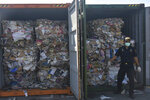 Custom officers stand near containers of waste at Tanjung Perak port in Surabaya, East Java, Indonesia, Tuesday, July 9, 2019. Indonesia is sending dozens of containers of imported waste back to Western nations after finding it was contaminated with used diapers, plastic and other materials, adding to a growing backlash in Southeast Asia against being a dumping ground for the developed world's rubbish. (AP Photo)