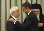 Greece's newly-letted prime minister Kyriakos Mitsotakis, right, talks with Greek President Prokopis Pavlopoulos, shortly after his swearing0-n ceremony at the Presidential Palace in Athens, Monday, July 8, 2019. Mitsotakis' New Democracy party won 39.8% of the vote, giving him 158 seats in the 300-member parliament, a comfortable governing majority. (AP Photo/Petros Giannakouris)