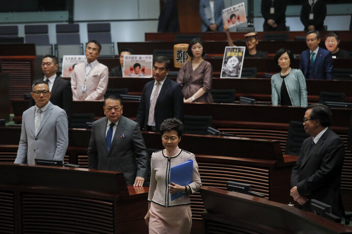 Hong Kong Chief Executive Carrie Lam, center, walks into Legislative Council in Hong Kong Wednesday, Oct. 16, 2019. In chaotic scenes, furious pro-democracy lawmakers twice forced Hong Kong's leader to stop delivering a speech laying out her policy objectives and clamored for her to resign after she walked out of the legislature on Wednesday and then delivered the annual address 75 minutes late via television. (AP Photo/Kin Cheung)
