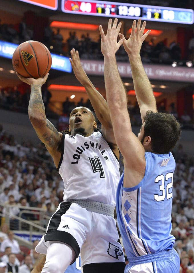 Louisville guard Khwan Fore (4) attempts a shot over the defense of North Carolina forward Luke Maye (32) during the second half of an NCAA college basketball game in Louisville, Ky., Saturday, Feb. 2, 2019. North Carolina won 79-69. (AP Photo/Timothy D. Easley)