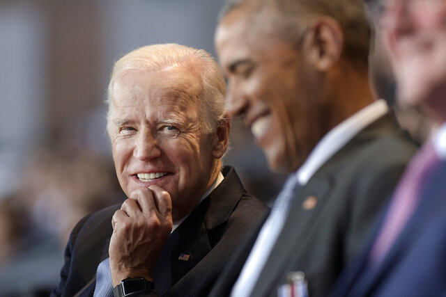 FILE - In this Jan. 4, 2017 file photo, Vice President Joe Biden, left, watches President Barack Obama, center, at Conmy Hall, Joint Base Myer-Henderson Hall, Va. Democrats hoping to create a surge of enthusiasm behind Joe Biden's presidential bid will look to Wednesday's convention headliners to broaden the party's focus from a rebuke of President Donald Trump to a message of change. Former President Barack Obama has top billing for the third night of the all-virtual Democratic National Convention. (AP Photo/Susan Walsh)