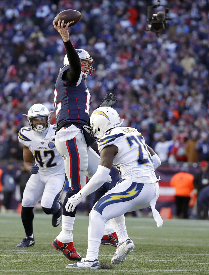 New England Patriots quarterback Tom Brady passes between Los Angeles Chargers linebacker Uchenna Nwosu (42) and defensive back Desmond King (20) during the second half of an NFL divisional playoff football game, Sunday, Jan. 13, 2019, in Foxborough, Mass. (AP Photo/Elise Amendola)