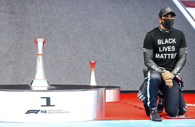 Mercedes driver Lewis Hamilton of Britain takes the knee beside the trophy prior the the Hungarian Formula One Grand Prix race at the Hungaroring racetrack in Mogyorod, Hungary, Sunday, July 19, 2020. (Mark Thompson/Pool via AP)