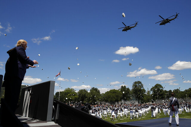 President Donald Trump applauds as Army helicopters fly over and West Point cadets toss their caps into the air at the end of commencement ceremonies on the parade field, at the United States Military Academy in West Point, N.Y., Saturday, June 13, 2020. (AP Photo/Alex Brandon)
