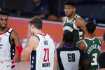 Washington Wizards' Moritz Wagner (21) grabs his face after getting head butted by Milwaukee Bucks' Giannis Antetokounmpo, rear, during the first half of an NBA basketball game, Tuesday, Aug. 11, 2020, in Lake Buena Vista, Fla. Antetokounmpo was ejected from the game. (AP Photo/Ashley Landis, Pool)
