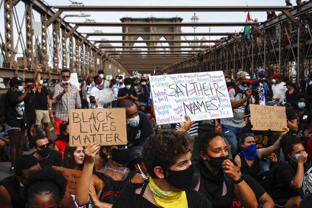 Protesters take a knee before continuing their march on the Brooklyn Bridge after attending a memorial service for George Floyd, on Thursday, June 4, 2020, in the Brooklyn borough of New York. Floyd, an African American man, died on May 25 after a white Minneapolis police officer pressed a knee into his neck for several minutes even after he stopped moving and pleading for air. (AP Photo/John Minchillo)