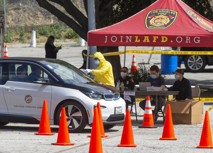 First responders who were scheduled to be tested earlier for COVID-19, get test kits at a drive-up testing site in Elysian Park, Los Angelas Thursday, April 2, 2020. Officials say hand-washing and keeping a safe social distance are priorities in battling the COVID-19 virus. (AP Photo/Damian Dovarganes)
