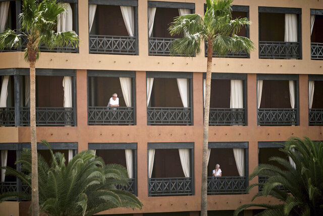 People stand at their balconies at the H10 Costa Adeje Palace hotel in Tenerife, Canary Island, Spain, Tuesday, Feb. 25, 2020. Spanish officials say a tourist hotel on the Canary Islands has been placed in quarantine after an Italian doctor staying there tested positive for the new coronavirus. (AP Photo)
