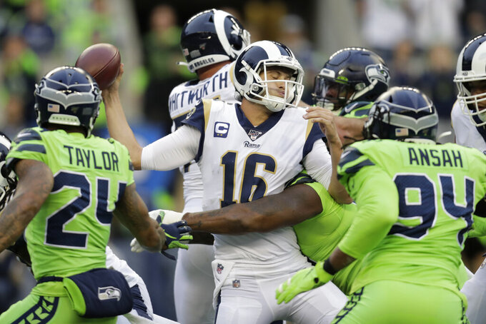 Los Angeles Rams quarterback Jared Goff, center, is tackled by Seattle Seahawks defensive tackle Quinton Jefferson, obscured, during the first half of an NFL football game Thursday, Oct. 3, 2019, in Seattle. (AP Photo/Stephen Brashear)