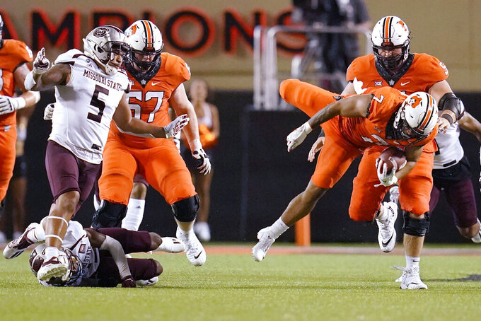 Oklahoma State running back Jaylen Warren (7) is sent to the turf on a carry against Missouri State during the second half of an NCAA college football game Saturday, Sept. 4, 2021, in Stillwater, Okla. (AP Photo/Sue Ogrocki)