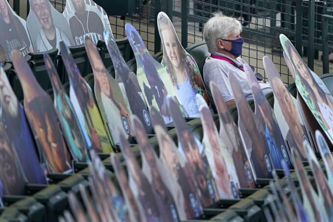 John Stanton, owner of the Seattle Mariners, wears a mask he he sits next to cutout photos of fans in the stands while watching the team's baseball game against the Texas Rangers, Saturday, Sept. 5, 2020, in Seattle. (AP Photo/Ted S. Warren)