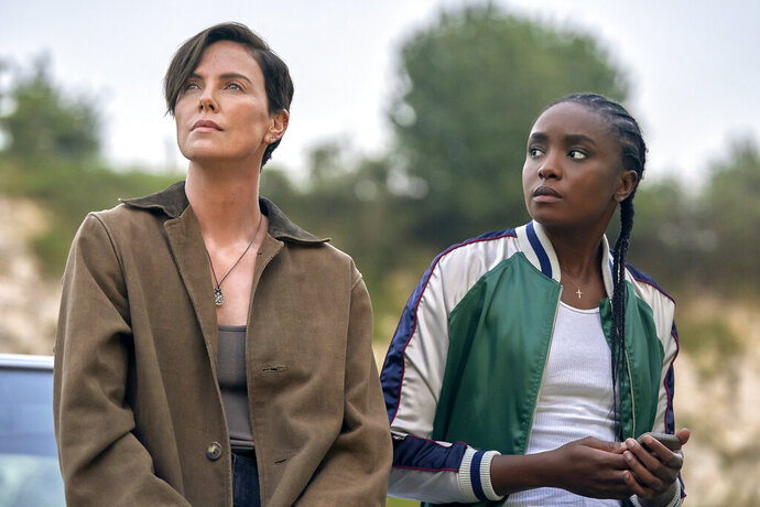 This image released by Netflix shows Charlize Theron, left, and Kiki Layne in a scene from