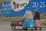 In this Jan. 18, 2020 photo, women walk past a mural promoting the re-election of Bolivia's former President Evo Morales, in El Alto, Bolivia.