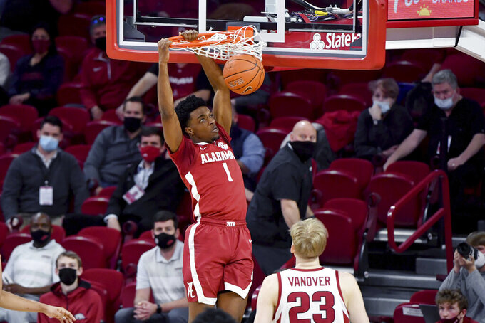 Alabama forward Herbert Jones (1) dunks the ball over Arkansas forward Connor Vanover (23) during the first half of an NCAA college basketball game in Fayetteville, Ark. Wednesday, Feb. 24, 2021. (AP Photo/Michael Woods)