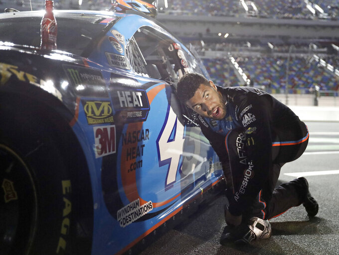 Darrell Wallace Jr. adjusts his driving shoes before getting into his car before the first of two qualifying auto races for the NASCAR Daytona 500 at Daytona International Speedway, Thursday, Feb. 14, 2019, in Daytona Beach, Fla. (AP Photo/John Raoux)