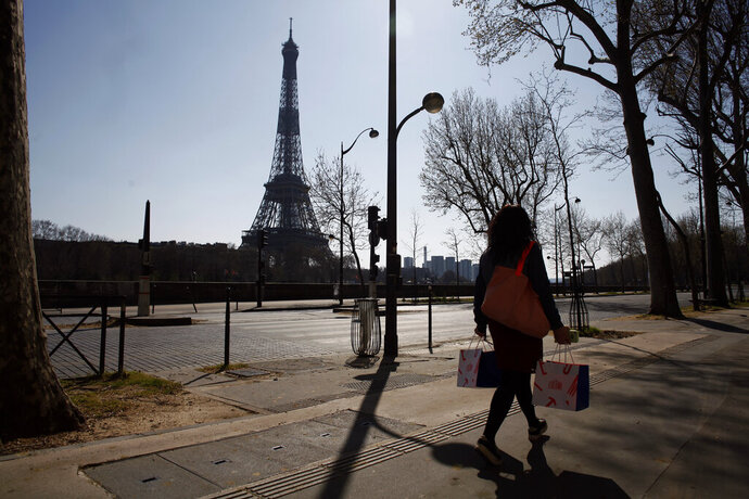A woman walks in an empty street near the Eiffel Tower during a nationwide confinement to counter the new coronavirus, in Paris, Thursday, March 26, 2020. The new coronavirus causes mild or moderate symptoms for most people, but for some, especially older adults and people with existing health problems, it can cause more severe illness or death. (AP Photo/Thibault Camus)