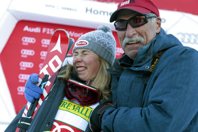 FILE - In this Nov. 25, 2015, file photo, first place finisher United States' Mikaela Shiffrin poses with her father Jeff Shiffrin after a women's World Cup slalom ski race in Aspen, Colo. When she's not winning races, two-time Olympic champion Mikaela Shiffrin unplugs by singing and playing guitar. Music was always a bond she shared with her late father, Jeff, who died on Feb. 2 after an accident at his home in Edwards, Colorado. Now music has become her escape.(AP Photo/Nathan Bilow, File)