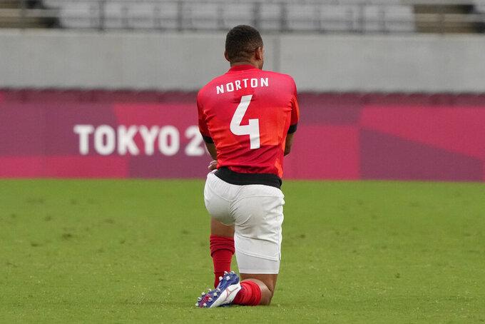 Britain's Dan Norton kneels before their men's rugby sevens quarterfinal match against the U.S. at the 2020 Summer Olympics, Tuesday, July 27, 2021, in Tokyo. (AP Photo/Shuji Kajiyama)