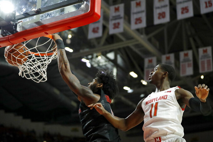 Rutgers center Myles Johnson, left, dunks next to Maryland guard Darryl Morsell during the first half of an NCAA college basketball game Tuesday, Feb. 4, 2020, in College Park, Md. (AP Photo/Julio Cortez)