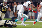 Miami Dolphins running back Mark Walton (9) carries as New Orleans Saints defensive back Chris Banjo (31) tries to tackle in the first half of an NFL preseason football game in New Orleans, Thursday, Aug. 29, 2019. (AP Photo/Gerald Herbert)