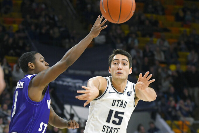 Utah State guard Abel Porter (15) passes the ball away from Weber State guard KJ Cunningham during an NCAA college basketball game Friday, Nov. 8, 2019, in Logan, Utah. (AP Photo/Eli Lucero)