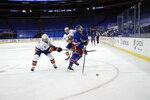 New York Islanders' Jordan Eberle, left, hits New York Rangers' Julien Gauthier during the second period of an NHL hockey game Thursday, Jan. 14, 2021, in New York. (Bruce Bennett/Pool Photo via AP)