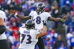 El quarterback de los Ravens de Baltimore Lamar Jackson celebra una jugada de touchdown de 61 yardas con su compañero Marshal Yanda en la segunda mitad del juego ante los Bills de BUffalo el domingo 8 de diciembre de 2019, en Orchard Park, Nueva York. (AP Foto/John Munson)