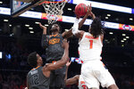 Oklahoma State forward Kalib Boone (22) goes to the basket against Syracuse forward Quincy Guerrier (1) during the first half of an NCAA college semi final basketball game in the NIT Season Tip-Off tournament, Wednesday, Nov. 27, 2019, in New York. (AP Photo/Mary Altaffer)