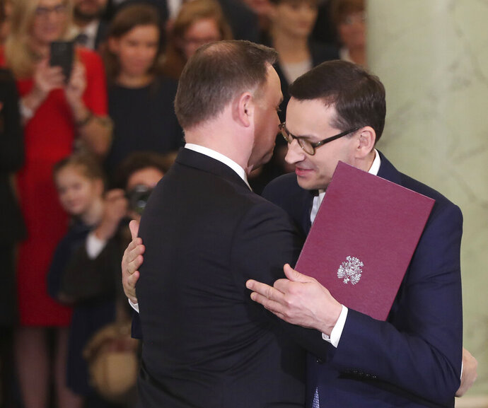 Poland's President Andrzej Duda,right, takes the oath of office from Prime Minister Mateusz Morawiecki and members of the new government that Morawiecki formed, following last month's election that gave the ruling right-wing Law and Justice party a second term in power, at the Presidential Palace in Warsaw, Poland, Friday, Nov. 15, 2019. Morawiecki and his Cabinet still need approval from the parliament, expected next week. (AP Photo/Czarek Sokolowski)