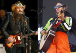 Chris Stapleton performs at the 50th annual CMA Awards on Nov. 2, 2016, in Nashville, Tenn., left, and H.E.R. performs at Lollapalooza on Aug. 1, 2019, in Chicago.  Stapleton and fellow guitar slayer H.E.R. are joining forces onstage at Wednesday's CMT Music Awards show celebrating the year's best country music videos. The event will air at 8 p.m. Eastern. (AP Photo)