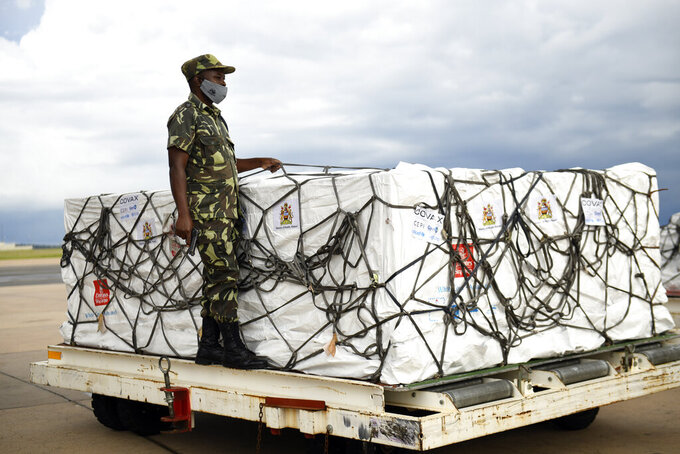 FILE - In this Friday, March 5, 2021 file photo, a Malawian policeman guards AstraZeneca COVID-19 vaccines after the shipment arrived at the Kamuzu International Airport in Lilongwe, Malawi. Some Africans are hesitating to get COVID-19 vaccines amid concerns about their safety, alarming public health officials as some countries start to destroy thousands of doses that expired before use. (AP Photo/Thoko Chikondi, File)