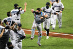 Miami Marlins catcher Francisco Cervelli, center, reacts he engages with teammates in a social distant celebration after defeating the Baltimore Orioles 4-0 during a baseball game, Tuesday, Aug. 4, 2020, in Baltimore. (AP Photo/Julio Cortez)