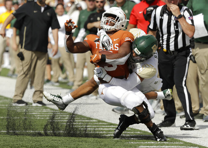 Texas running back Tre Watson (5) is hit by Baylor safety Blake Lynch, front right, after making a catch during the first half of an NCAA college football game, Saturday, Oct. 13, 2018, in Austin, Texas. (AP Photo/Eric Gay)