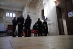 French police officers and lawyers gather in the entrance hall on the opening day of the trial