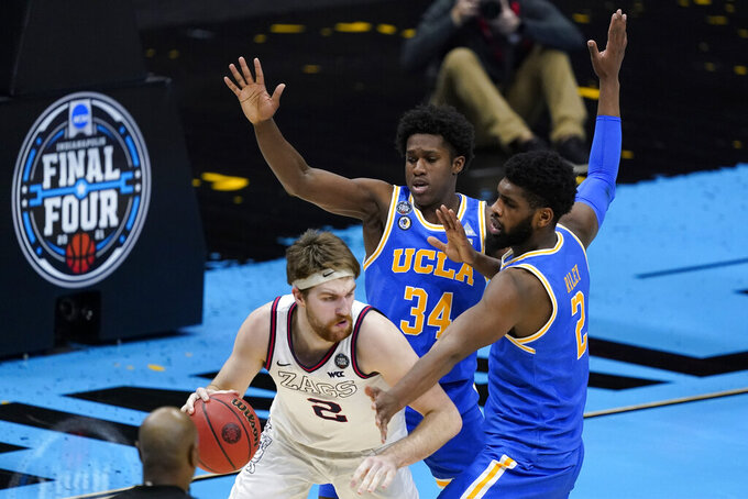 Gonzaga forward Drew Timme, left, dribbles around UCLA guard David Singleton (34) and forward Cody Riley, right, during the second half of a men's Final Four NCAA college basketball tournament semifinal game, Saturday, April 3, 2021, at Lucas Oil Stadium in Indianapolis. (AP Photo/Darron Cummings)