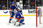 New York Islanders goaltender Semyon Varlamov (40) can't stop the puck shot by Tampa Bay Lightning's Yanni Gourde (not pictured) for a goal during the first period of Game 3 of the Stanley Cup semifinals, Thursday, June 17, 2021, in Uniondale, N.Y. New York Islanders defenseman Ryan Pulock (6) and Tampa Bay Lightning center Tyler Johnson (9) looked on. (AP Photo/Frank Franklin II)